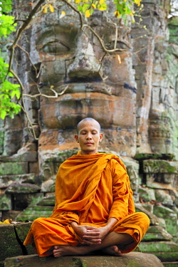 CMB1621AW Southeast Asia, Cambodia, Siem Reap, Angkor temples, Buddhist monk in saffron robes meditating (MR)