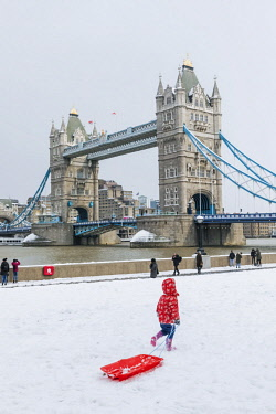 TPX64554 England, London, Southwark, Child Playing in the Snow with Tower Bridge in the Background