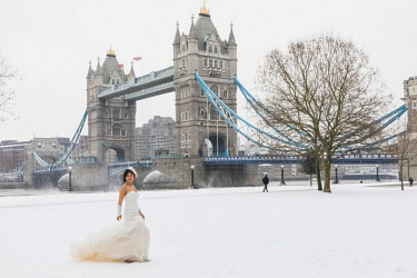 TPX64586 England, London, Southwark, Potters Field, Chinese Bride in Wedding Dress Posing in the Snow with Tower Bridge in the Background