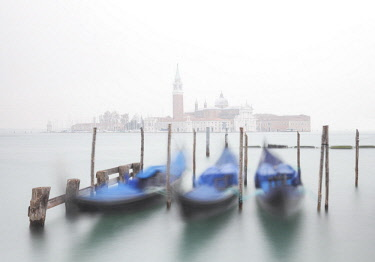ITA12785AW Gondolas moored at the Bacino di San Marco with a slightly visible Church of San Giorgio Maggiore, due to fog. Venice. Veneto. Italy.