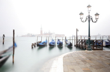 ITA12786AW Gondolas moored at the Bacino di San Marco with a slightly visible Church of San Giorgio Maggiore, due to fog. Venice. Veneto. Italy.