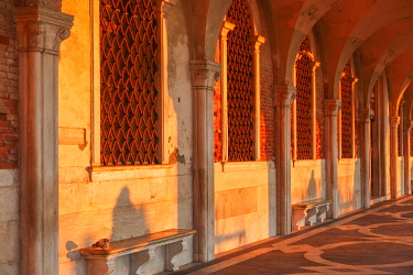 ITA12818AW Sun Rays at Sunrise through the Arches of Palazzo Ducale (Doge's Palace) St Mark Square, Venice, Veneto, Italy.