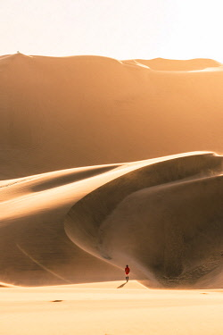 NAM6465AW Walvis Bay, Namibia, Africa. Man walking on the sand dunes at sunset.