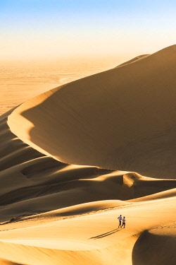 NAM6466AW Walvis Bay, Namibia, Africa. Tourists walking on the sand dunes at sunset.