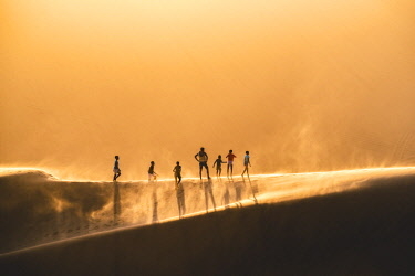NAM6467AW Walvis Bay, Namibia, Africa. People walking on the edge of a sand dune at sunset.