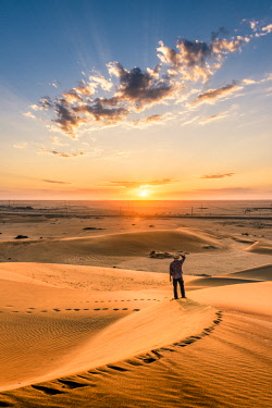 NAM6470AW Walvis Bay, Namibia, Africa. Tourist admiring the sunrise from the top of a sand dune.