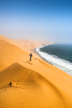 NAM6475AW Sandwich Harbor, Namib-Naukluft National Park, Namibia. Tourist admiring the ocean from the top of the sand dunes.