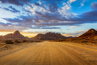 NAM6481AW Spitzkoppe, Damaraland, Namibia, Africa. Gravel road to the granite peaks at sunset.