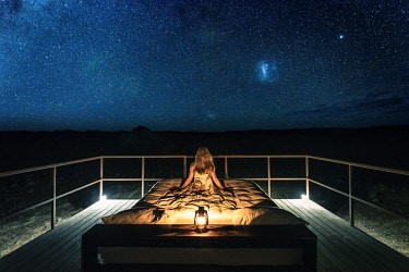 NAM6488AW Tourist sitting on a bed outdoor admiring the stars of the Southern Hemisphere, Namibia, Africa. Namib Dune Star Camp.
