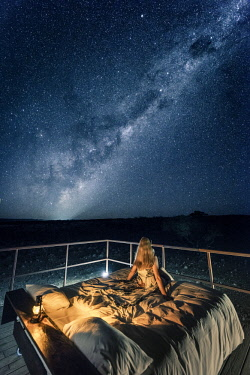 NAM6489AW Tourist sitting on a bed outdoor admiring the stars of the Southern Hemisphere, Namibia, Africa. Namib Dune Star Camp.