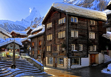 IBLGNG04646418 Typical old Valaisian houses at the church square in the back of Matterhorn 4478m, Zermatt, Mattertal, Valais, Switzerland, Europe