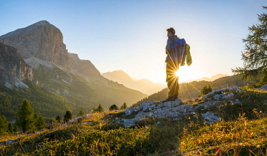 Hiker looking into the distance, sunrise, solar reflex in front of the Col dei Bos and Tofane peaks, Falzarego Pass, Dolomites, South Tyrol, Trentino-Alto Adige, Italy, Europe