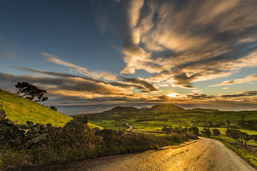 IBXSEI04644440 Road through green hilly countryside at sunrise with clouds, island of Pico, Azores, Portugal, Europe