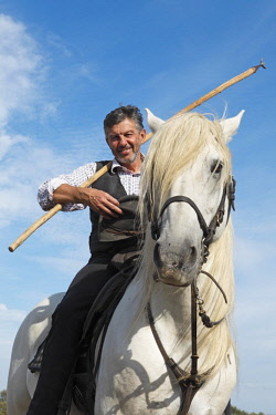IBXCXB04616928 Gardian or traditional bull herder in typical working clothes on a Camargue horse, Le Grau-du-Roi, Camargue, France, Europe