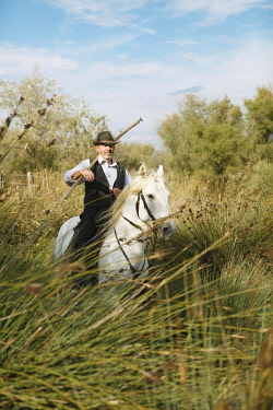 IBXCXB04616934 Gardian or traditional bull herder in typical working clothes galloping on a Camargue horse, Le Grau-du-Roi, Camargue, France, Europe