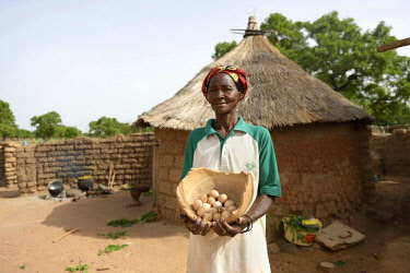 IBLFLK04517656 Woman, farmer proudly showing eggs from her chickens, Toeghin village, Oubritenga province, Plateau Central region, Burkina Faso, Africa *** IMPORTANT: Use by development aid organizations in Germany...
