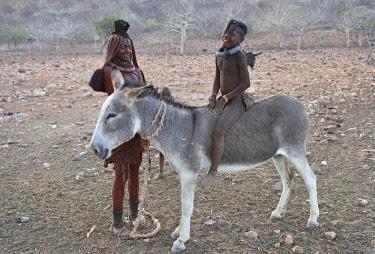 IBLWWI04619254 Married Himbafrau with girl on a donkey, Kaokoveld, Namibia, Africa