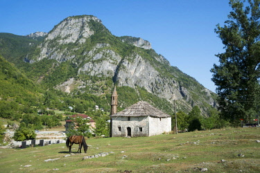 IBXFSC04601756 Horse grazes in front of mosque, near Margegej, Albanian Alps, Albania, Europe