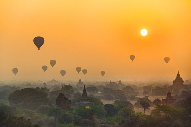 IBXVFW04409703 View of pagodas with hot air balloons, temples, sunrise, haze, morning light, Bagan, Division Mandalay, Myanmar, Asia