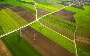 IBXMIR04361439 High-voltage transmission lines over farm fields in spring, aerial view, in Moosinning, Upper Bavaria, Bavaria, Germany, Europe