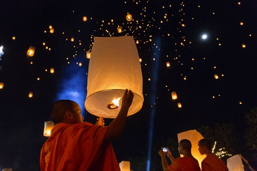 IBLSBE04340878 Monk letting sky lantern rise, Loi Kratong or Loy Krathong festival, night sky, Chiang Rai Province, Thailand, Asia