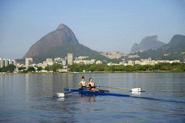 IBLFLK04403194 Two young women participating in early morning rowing training in the Lagoa Rodrigo de Freitas Lagoon, with Rio de Janeiro skyline and Sugar Loaf Mountain, Lagoa District, Rio de Janeiro, Brazil, Sout...
