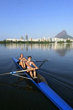 IBLFLK04403209 Two young women participating in early morning rowing training in the Lagoa Rodrigo de Freitas Lagoon, with Rio de Janeiro skyline and Sugar Loaf Mountain, Lagoa District, Rio de Janeiro, Brazil, Sout...