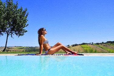 IBLATF04407657 Woman sunbathing in bikini by a pool, Morro D'Alba, Ancona, Marche, Italy, Europe