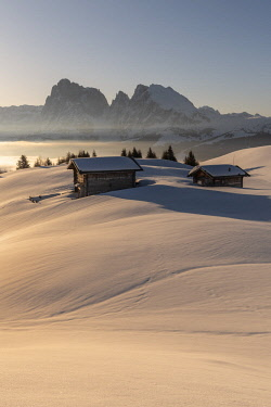 CLKMK88381 Alpe di Siusi/Seiser Alm, Dolomites, South Tyrol, Italy. Sunrise on the plateau of Bullaccia/Puflatsch. In the background the peaks of the Sella and  Sassolungo