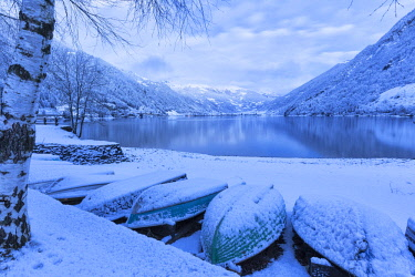 CLKFB84722 Boats covered by snow at Poschiavo Lake during twilight. Poschiavo Lake, Poschiavo Valley (Val Poschiavo), Graubunden, Switzerland.