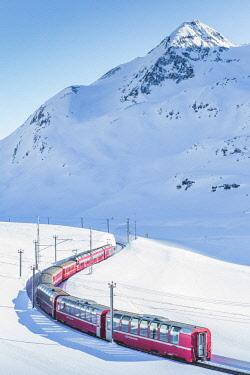 CLKFV83529 Bernina Express red train passing Lago Bianco in a scenic winter mountain landscape, Graubunden, Switzerland