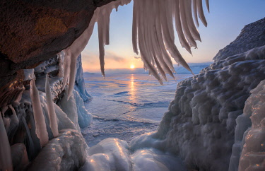 CLKYV84364 Ice stalactites in a cave at the shore at sunset at lake Baikal, Irkutsk region, Siberia, Russia
