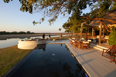 ZAM8108 Zambia, South Luangwa National Park, Chinzombo Camp. Chinzombo's dining and sit-out areas overlook the sandy banks of the Luangwa River.