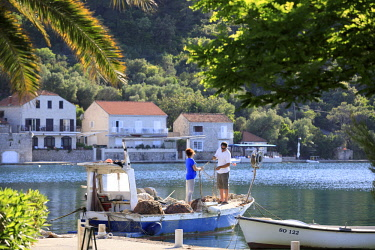 CRO1724AW Croatia, Dalmatia, Sipan. Fisherman mending nets in the harbour at Sipanska Luka.