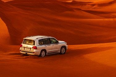 UAE0775 Four wheel drive dune bashing in the Sharjah Desert Dunes at sunset, Sharjah, United Arab Emirates.