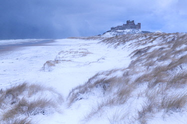ENG15655AW Snow covered beach and sand dunes by Bamburgh Castle, Northumberland, England. Winter (February) 2018.
