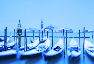 ITA13050 Venice. Veneto. Italy. Gondolas moored on the bacino di San Marco with the island of San Giorgio Maggiore with snow.
