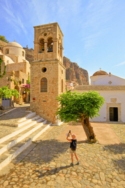 GR240RF Tourist Taking Photograph of The Church of Elkomenos Christos and Bell Tower in Platia Dsami Square, Monemvasia, Laconia, The Peloponnese, Greece, Southern Europe