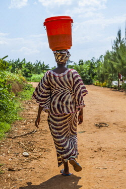ARTOFA000225 Rear view of African woman carrying bucket on head, Kigali, Rwanda