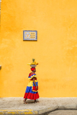 HMS2601889 Colombia, Bolivar department, Cartagena, historical center listed as World Heritage by UNESCO, district of Centro, Santo Domingo Church, traditional costume woman carrying fruit