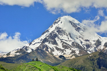 GEO0354AWRF Mount Kazbek (5047m), the third-highest peak in Georgia, bordering Russia, with the Gergeti Trinity Church on its slopes. Khevi-Kazbegi region. Georgia, Caucasus