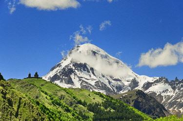 GEO0356AWRF Mount Kazbek (5047m), the third-highest peak in Georgia, bordering Russia, with the Gergeti Trinity Church on its slopes. Khevi-Kazbegi region. Georgia, Caucasus