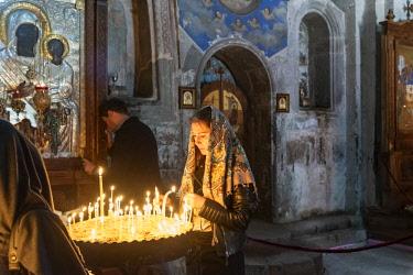 GEO0310AW Devotion and faith at the Gergeti Trinity Church (Tsminda Sameba) dating back to the 14th century. Khevi-Kazbegi region. Georgia, Caucasus