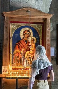 GEO0311AW Devotion and faith at the Gergeti Trinity Church (Tsminda Sameba) dating back to the 14th century. Khevi-Kazbegi region. Georgia, Caucasus