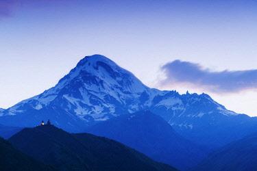GEO0314AW Mount Kazbek (5047m), the third-highest peak in Georgia, bordering Russia, with the Gergeti Trinity Church on its slopes. Khevi-Kazbegi region. Georgia, Caucasus