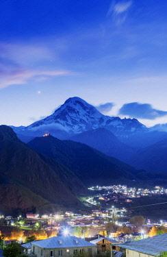 GEO0315AW Mount Kazbek (5047m), the third-highest peak in Georgia, bordering Russia, with the Gergeti Trinity Church on its slopes and the village of Stepantsminda at dusk. Khevi-Kazbegi region. Georgia, Caucas...