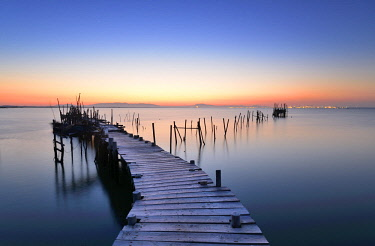 POR9806AW Wooden pillars piers, a palafite fishing harbour of Carrasqueira at dusk. Alentejo, Portugal