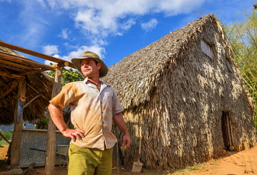 HMS3048746 Cuba, Pinar del Rio province, Vinales, Vinales national park, Vinales valley, a UNESCO World Heritage site, farmer in front of his tobacco dryer