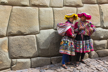 HMS2356795 Peru, Cusco Province, Cusco, listed as World Heritage by UNESCO, women in traditional dress near a stone Inca wall