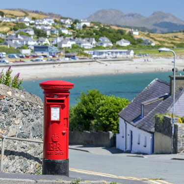 WAL7643AW Wales, Gwynedd, Criccieth. Red letter box and a sandy beach in the distance.